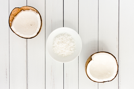 Two coconut halves and coconut flakes in a white porcelain bowl on white wood panel background with copy space. Top view.