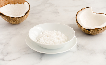 Coconut halves and coconut flakes in a white porcelain bowl on white marble background with copy space. Angled view.