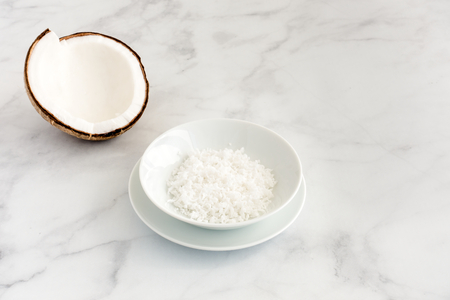 Coconut half and freshly grated coconut flakes in a white porcelain bowl on white marble background with copy space.