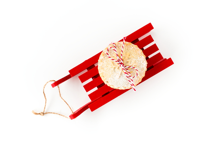 Mince Pie on a red wooden sledge isolated on white background. Top view.