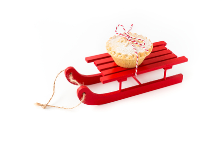 Red wooden sledge with Mince Pie isolated on white background. Angled view. Banque d'images