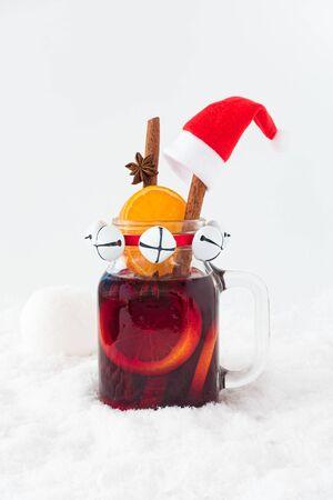 Vin chaud avec décoration de Noël dans la neige avec boule de neige. Espace de copie et vue en contre-plongée.