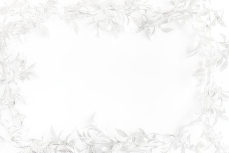 Christmas frame with silver glitter leaves on white background. Top view.