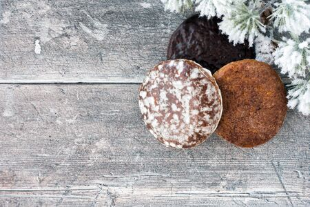 German gingerbread, Lebkuchen, on rustic brown wood panel background with snow covered fir twig and lots of copy space. Top view.