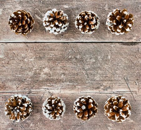 Christmas background with pine cones on brown rustic wood. Top view.