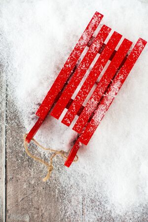 Top view of a red sledge covered with snowflakes in snow and on brown rustic wood panel background with copy space.