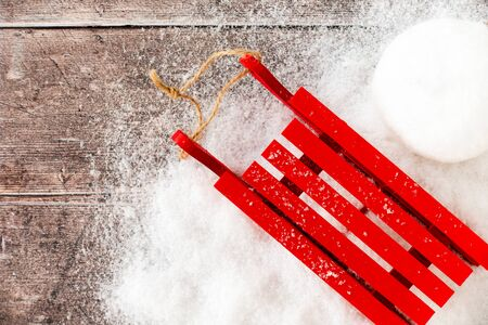 Red sledge and a snowball in snow and on brown rustic wood panel background with copy space. Top view.