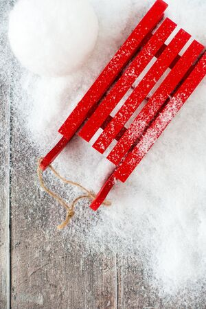 Top view of a red sledge and a snowball in snow and on brown rustic wood panel background with copy space. 版權商用圖片