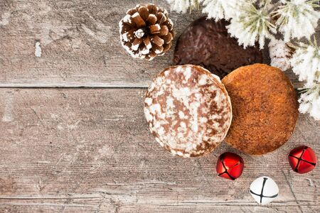 Variety of German Lebkuchen, gingerbread with jingle bells, pine cone and snow covered evergreen branch on rustic brown wood panel background with copy space. Top view.