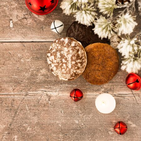 Lebkuchen, german gingerbread with jingle bells, tealight and snow covered evergreen branch on rustic brown wood panel background with copy space. Top view.