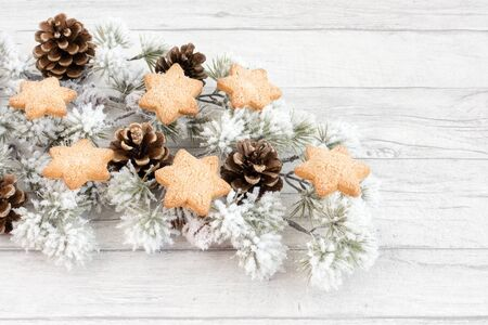 Christmas cookies on snow covered atlas cedar branch and pine cones on white wood panel background with copy space. Angled view.