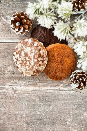 Nuremberg Lebkuchen, German Gingerbread with pine cones and snow covered cedar fir tree twig on rustic brown wood panel background with copy space. Top view.