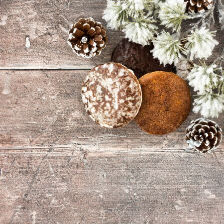 German Gingerbread, Nuremberg Lebkuchen, with pine cones and snow covered cedar fir tree twig on rustic brown wood panel background with copy space. Top view.