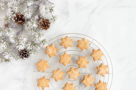 Christmas star cookies in cooling rack with evergreen branch and pine cones on white marble background with copy space. Top view. Reklamní fotografie