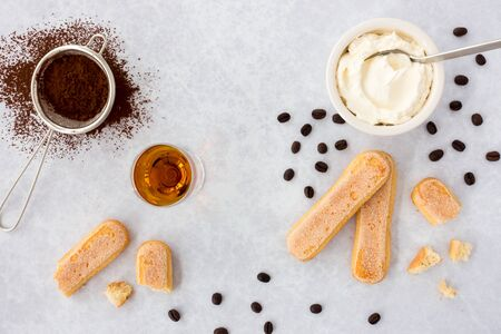 Tiramisu ingredients, ladyfingers, mascarpone, cocoa, almond liqueur and scattered black coffee beans on gray textured background with copy space. Top view. 版權商用圖片