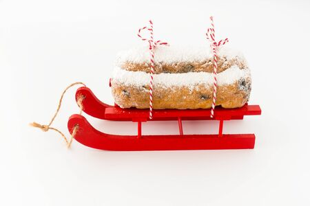 Close-up of Christstollen, a German stollen, on red wooden sledge isolated on white. Low angled view.