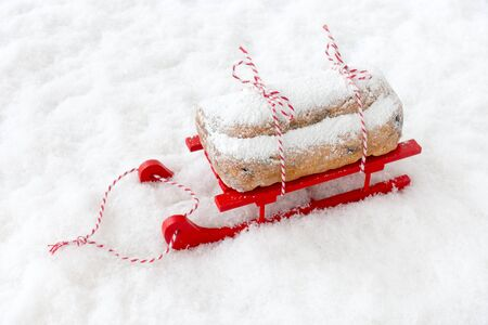 Dresdner stollen, a German Christstollen, on red wooden sledge in snow with copy space. High angle view.