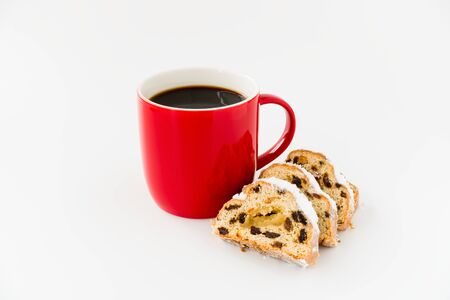 Stollen slices and red mug filled with black coffee isolated on white background. Angled view.