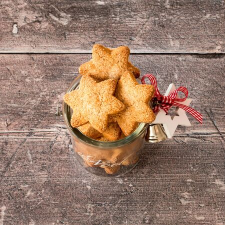 Christmas cookies in homemade glass jar with Christmas decoration on rustic, weathered, brown wood panel background. High angle view.