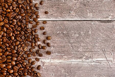 Roasted coffee beans on dark brown rustic weathered wood panel background with lots of copy space. Top View. 版權商用圖片