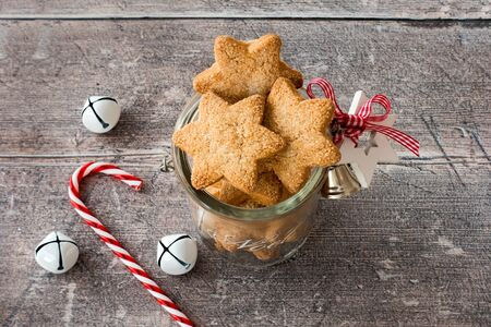 Christmas cookies in homemade glass jar with Christmas decoration, jingle bells and candy cane on rustic, weathered, brown wood panel background. High angle view.