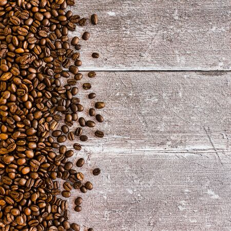 Medium dark roasted coffee beans on dark brown rustic weathered wood panel background with lots of copy space. Top View.