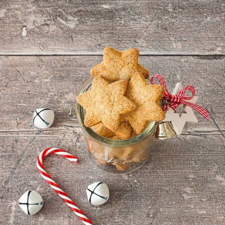 Christmas cookies in decorated glass jar with Christmas with candy cane and jingle bells on rustic, weathered, brown wood panel background. High angle view.