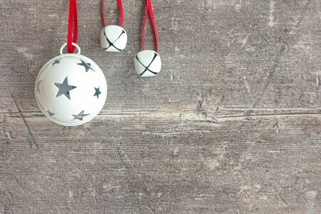 Closeup of three white hanging jingle bells on dark brown, rustic weathered wood with copy space. Top view.