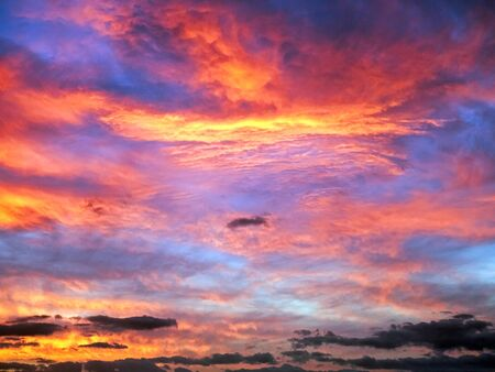 Dramatic, cloudy sunrise sky in dark magenta, purple, red, orange and yellow colors with sun and sun rays.