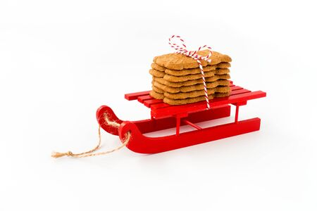 Spekulatius, Speculaas, Speculoos, spiced Christmas cookies on red wooden sledge isolated on white. Angled view. 版權商用圖片