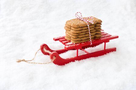 Biscuits de Noël épicés appelés Spekulatius, Speculaas, Speculoos, en Allemagne, aux Pays-Bas et en France, sur un traîneau en bois rouge dans la neige. Banque d'images