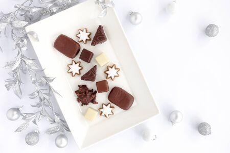 Assortment of German gingerbread, Lebkuchen, on white serving plate with silver leaf garland and silver Christmas baubles on white background. Top view.