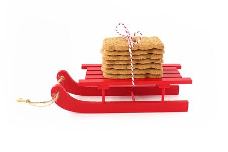 Spekulatius, Speculaas, Speculoos, spiced Christmas cookies on red wooden sledge isolated on white. Low Angle view.
