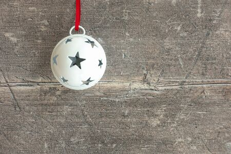 Closeup of a white hanging jingle bell on dark brown, rustic weathered wood with copy space. Top view. 版權商用圖片