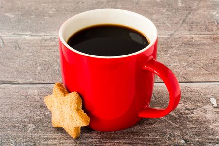 Red mug filled with black coffee and Christmas star cookie on rustic, weathered dark brown wood panel background.