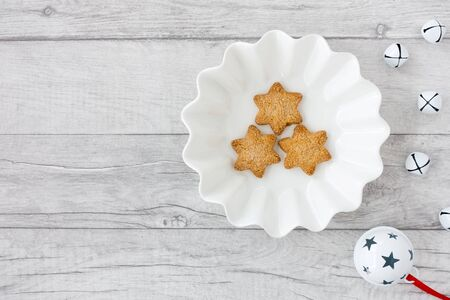Star shaped Christmas cookies in white bowl with jingle bells on white wood panel background with copy space. Top view. 版權商用圖片