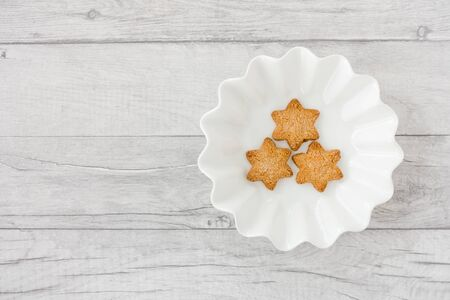 Star shaped Christmas cookies in bowl on white wood panel background with copy space. Top view. 版權商用圖片