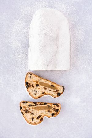 Christstollen, German Stollen filled with marzipan and two cut slices directly on background with icing sugar.