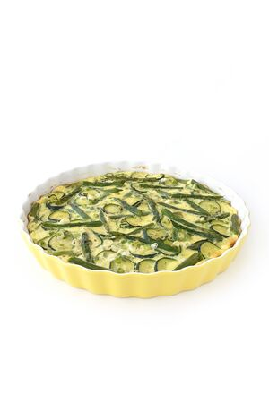Homemade asparagus and zucchini quiche with spring onions isolated on white. High angle view. 版權商用圖片