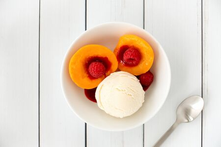 Top view of a Peach Melba sundae in a white porcelain bowl filled with vanilla ice cream, peaches, raspberries and raspberry sauce on white wood panel background with copy space.