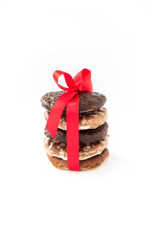 Stack of assorted, original nuremberg Lebkuchen, gingerbread with red bow and ribbon isolated on white background.