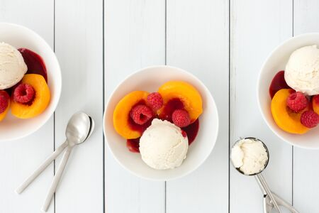 Bowls filled with vanilla ice cream, peaches, raspberries and raspberry sauce on white wood panel background with copy space. Top view.