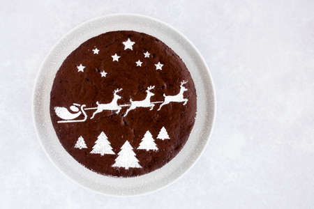Homemade chocolate cake with Christmas theme on grey background with lots of copy space.