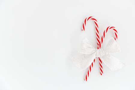Christmas background of two red candy canes with festive bow isolated on white background. Top view. 版權商用圖片