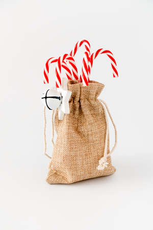 Red candy canes in jute sack with jingle bells and Christmas star isolated on white. Low angle view. 版權商用圖片
