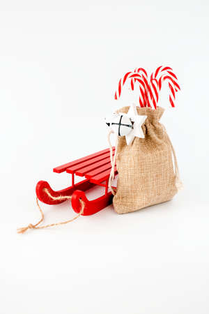Red sledge and candy canes in jute sack with jingle bells and Christmas star isolated on white.