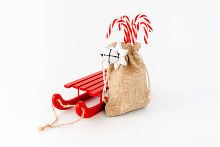 Sledge and candy canes in jute sack with jingle bells and Christmas star isolated on white with copy space. Stock Photo