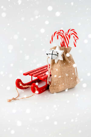 Red sledge and candy canes in jute sack with Christmas decoration and snow flakes. 版權商用圖片