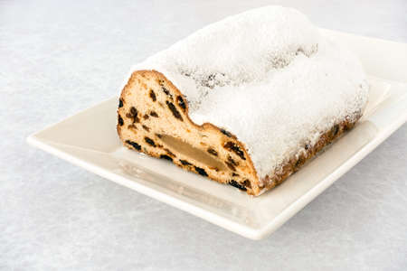 Closeup of half a Marzipan Christstollen, German Stollen, Weihnachtsstollen, on a white plate and grey textured background with copy space. Low angle view.