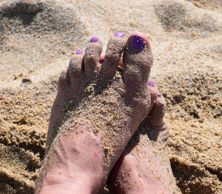 sandy toes in the sunshine, Close-up of womans pedicured feet and toes with pink nail polish covered with crystal sand Stock Photo
